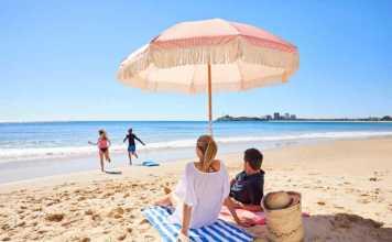 Couple under an umbrella on a Sunshine Coast beach