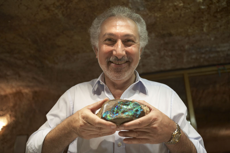 man holdeing a huge opal in coober pedy