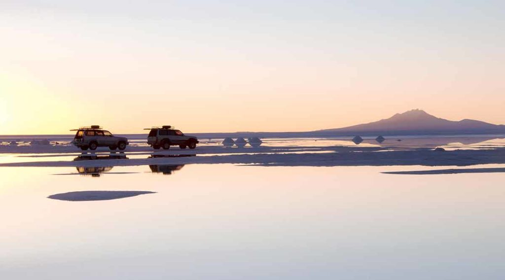 Vehicles reflected in Bolivia's salt flats